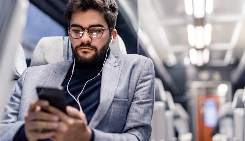 Podcasts: homem jovem escutando áudio em ônibus coletivo